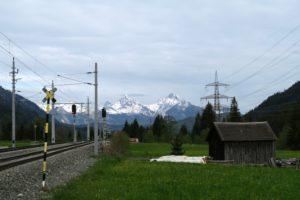 Eingerahmt von Hochspannungs- und Bahnstrecke grüßen die Tannheimer Berge aus der Ferne.