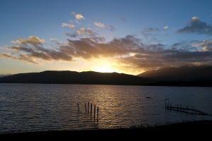 Hinter dem Lake Te Anau geht die Sonne unter.
